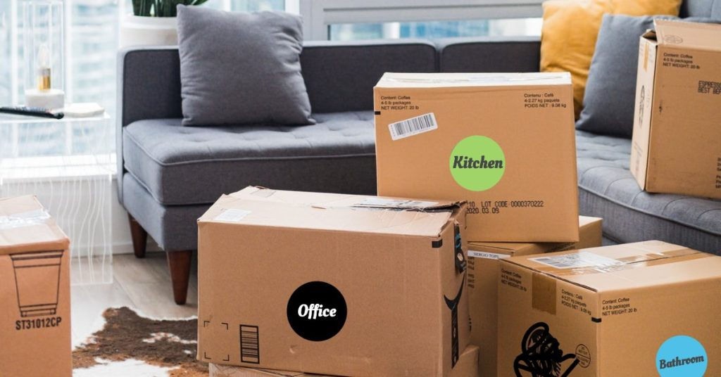 Color-coded moving boxes stacked in front of gray couch