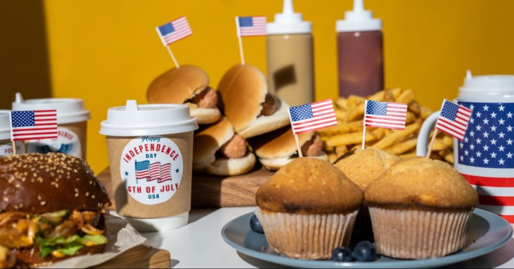 Close-up of a Fourth of July cookout with muffins, hot dogs, hamburger, & fries; all foods have American flag toothpick decoration; yellow background