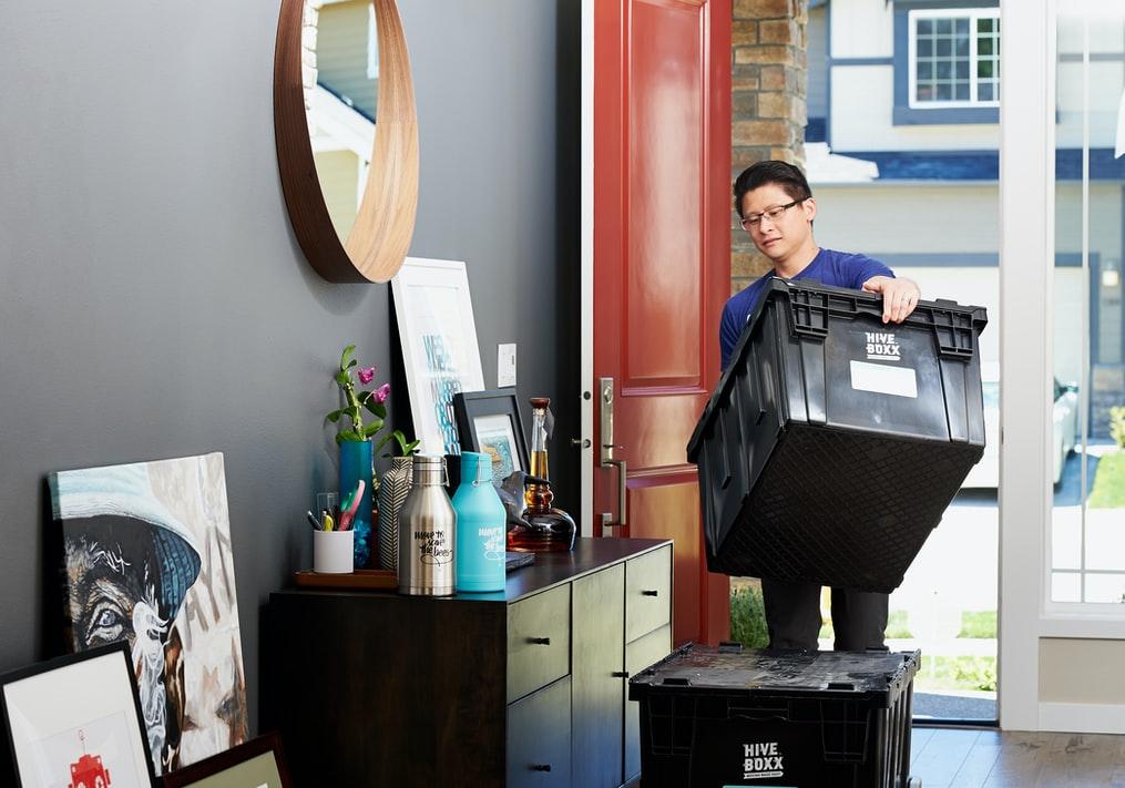 man moving storage bins